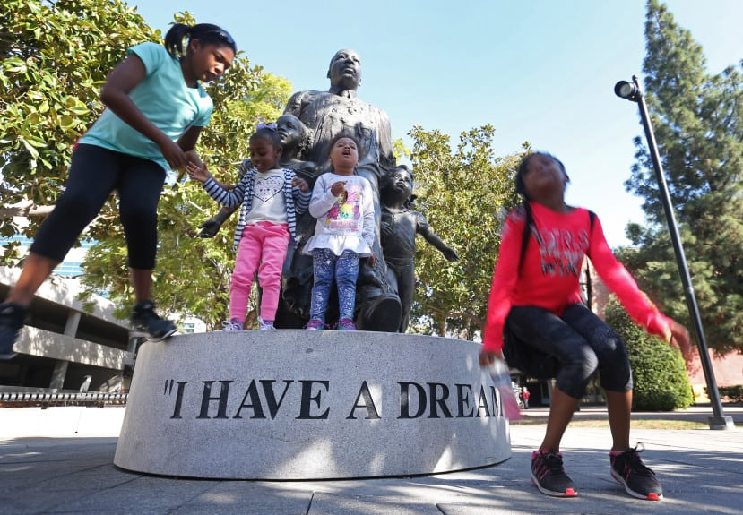 Cousins from left to right, Chanelle Chatham, 11, of Riverside, Kamili Sykes, 4, of Riverside, Aalaya Lucas, 3, of Riverside, and Sanii Foster, 8, of Moreno  Valley, finish posing for a photo with a statue of Martin Luther King Jr., after walking to the site during the 25th annual Martin Luther King Jr. Walk-a-Thon in Riverside on Monday, Jan. 15, 2017.  (Stan Lim, The Press-Enterprise/SCNG)